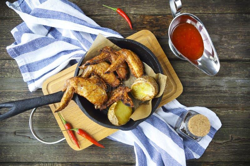 Ψημένα στη σχάρα φτερά κοτόπουλου με την κόκκινη πικάντικη σάλτσα στοκ εικόνες