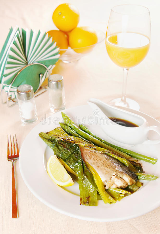 Ψημένα στη σχάρα ψάρια και σπαράγγι στο πιάτο στοκ εικόνες