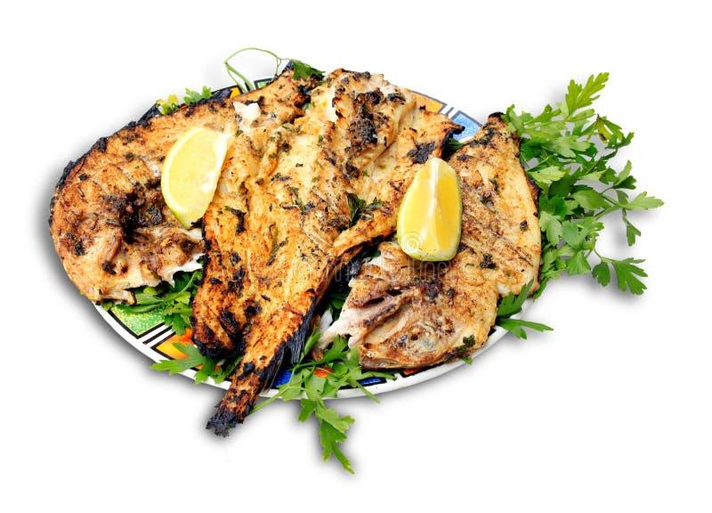 Ψημένα στη σχάρα ψάρια με τα πράσινα στο πιάτο στοκ εικόνες