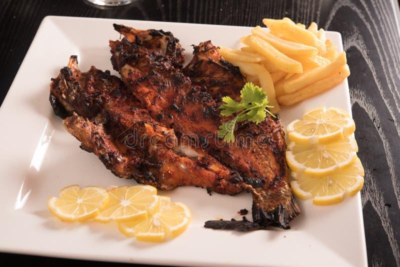 Ψημένα στη σχάρα ψάρια σε ένα άσπρο πιάτο που διακοσμείται με το κορίανδρο, τις τηγανιτές πατάτες και τις φέτες λεμονιών στοκ φωτογραφίες