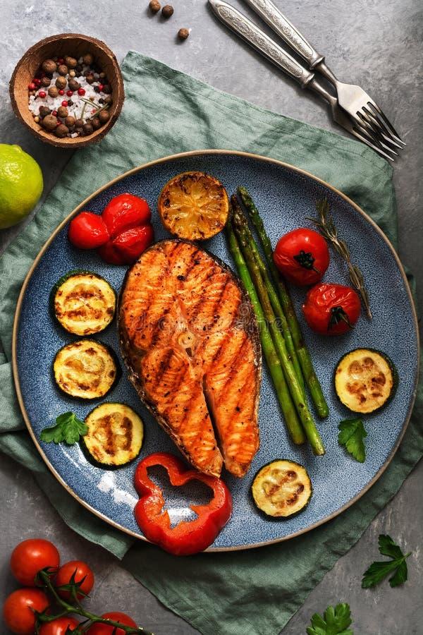 Ψημένα στη σχάρα ψάρια σολομών με τα κολοκύθια λαχανικών, σπαράγγι, ντομάτα, γλυκό πιπέρι σε ένα πιάτο, γκρίζο υπόβαθρο r στοκ φωτογραφία με δικαίωμα ελεύθερης χρήσης