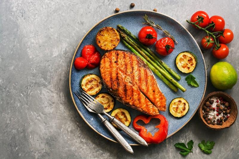 Ψημένα στη σχάρα ψάρια σολομών με τα κολοκύθια λαχανικών, σπαράγγι, ντομάτα, γλυκό πιπέρι σε ένα πιάτο, γκρίζο υπόβαθρο Η τοπ άπο στοκ εικόνα με δικαίωμα ελεύθερης χρήσης