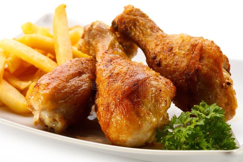 Ψημένα τυμπανόξυλα κοτόπουλου με τα τσιπ στοκ εικόνα