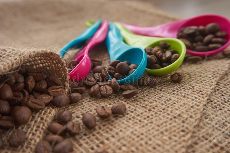 Ψημένα φασόλια καφέ, μετρώντας κουτάλια δόσεων στο σάκο γιούτας στοκ φωτογραφίες