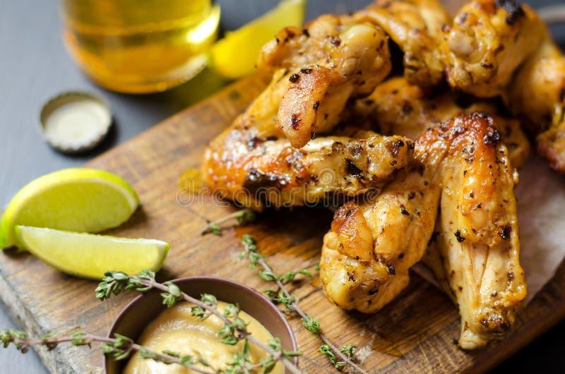 Ψημένα φτερά κοτόπουλου με τη μουστάρδα και τον ασβέστη, μπύρα στο υπόβαθρο στοκ εικόνες