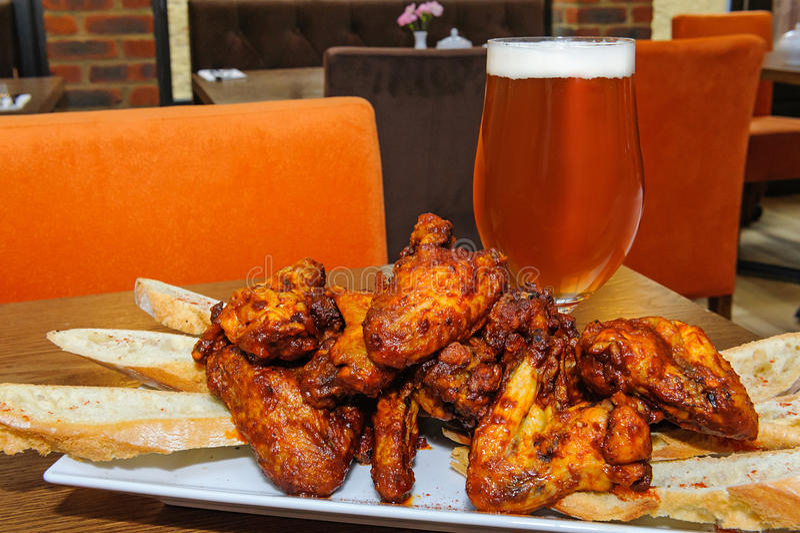 Ψημένα φτερά κοτόπουλου και ποτήρι της μπύρας στοκ εικόνα