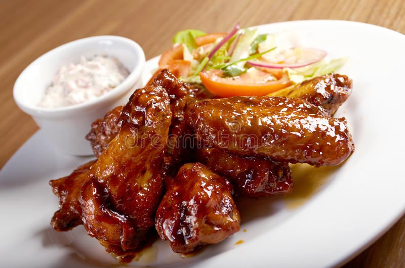 Ψημένα φτερά κοτόπουλου στο πιάτο στοκ εικόνες