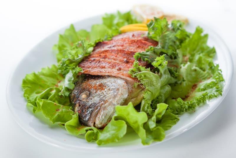 Ψημένα ψάρια και μπέϊκον με το μαρούλι και το λεμόνι. στο α  στοκ εικόνα με δικαίωμα ελεύθερης χρήσης