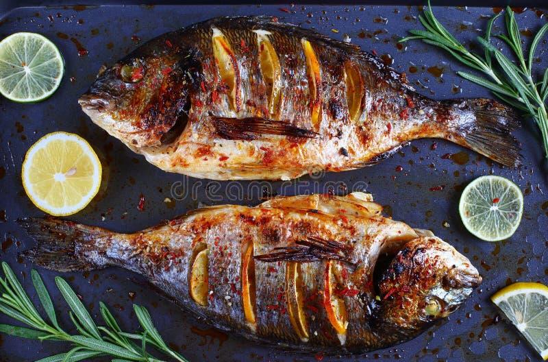 Ψημένα ψάρια τσιπουρών με τις φέτες λεμονιών στοκ φωτογραφία