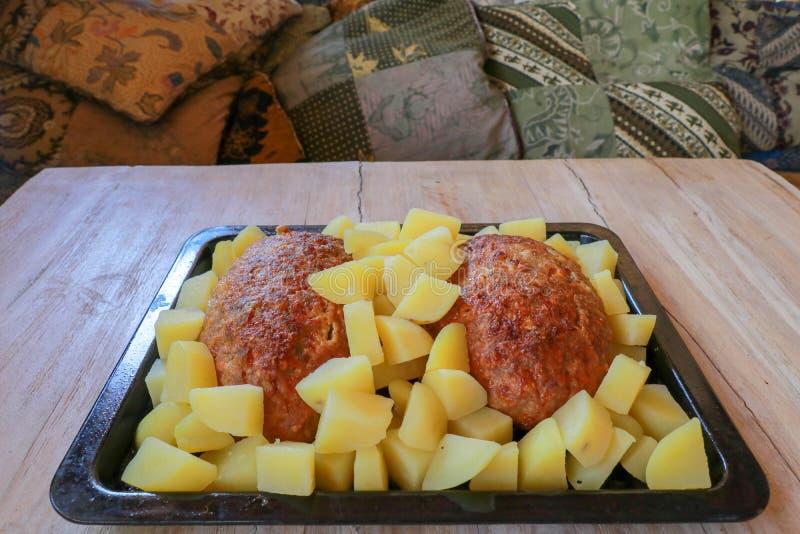 Ψημένες κομματιασμένες χοιρινό κρέας και πατάτες σε ένα μαύρο τηγάνι ψησίματος Τρόφιμα που τοποθετούνται στον ξύλινο πίνακα Υπόβα στοκ φωτογραφία με δικαίωμα ελεύθερης χρήσης
