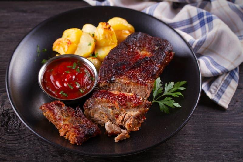 Ψημένες μπριζόλες χοιρινού κρέατος με τις πατάτες Ψημένο στη σχάρα κρέας στοκ εικόνα