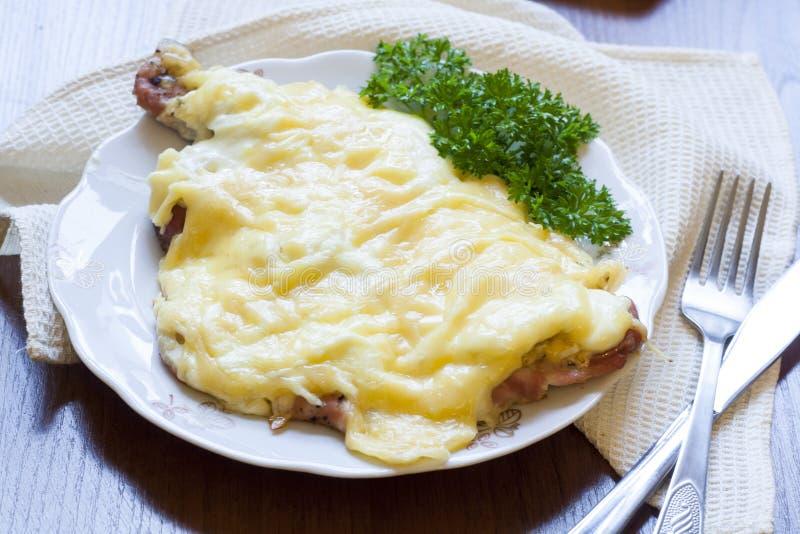 Ψημένες μπριζόλες χοιρινού κρέατος με το κρεμμύδι, τυρί μαγιονέζας με το φρέσκο μαϊντανό στο πιάτο στοκ εικόνα