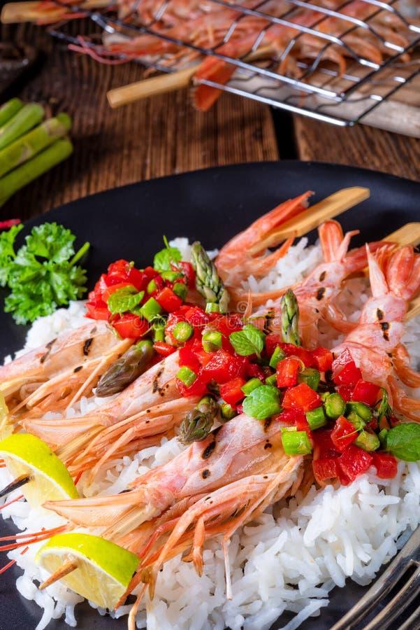 Ψημένες στη σχάρα κόκκινες αργεντινές γαρίδες με το κόκκινο salsa και το πράσινο σπαράγγι στοκ εικόνες