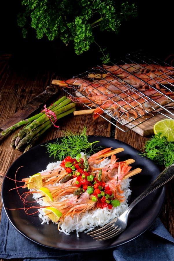 Ψημένες στη σχάρα κόκκινες αργεντινές γαρίδες με το κόκκινο salsa και το πράσινο σπαράγγι στοκ εικόνα
