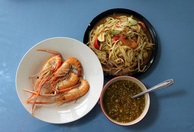 Ψημένες στη σχάρα μαγειρευμένες γαρίδες στο άσπρο πιάτο με τη σάλτσα στη σαλάτα κύπελλων και papaya στο μαύρο πιάτο στοκ εικόνες