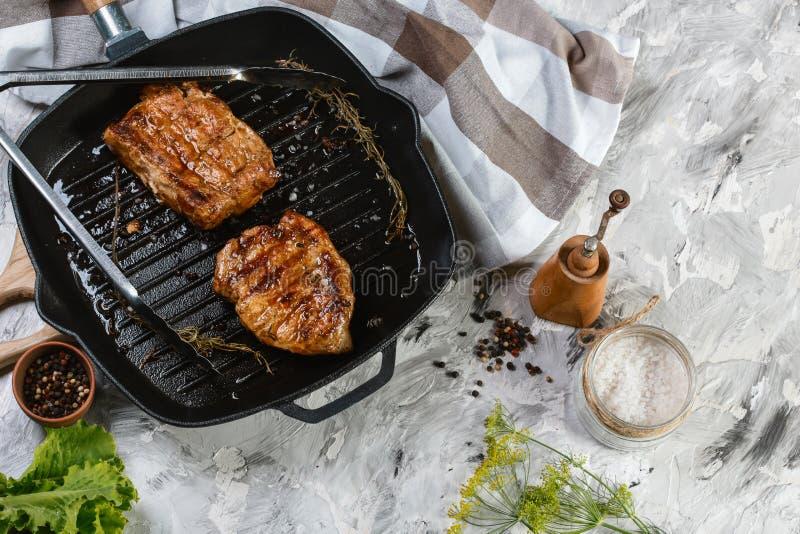 Ψημένες στη σχάρα μπριζόλες βόειου κρέατος με τα καρυκεύματα στο τηγάνι σιδήρου στον ξύλινο τέμνοντα πίνακα Τοπ άποψη με το διάστ στοκ φωτογραφία