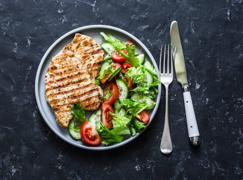 Ψημένες στη σχάρα μπριζόλες της Τουρκίας και ντομάτες, αγγούρια, σαλάτα πρασίνων σε ένα σκοτεινό υπόβαθρο, κορυφή υγιής έννοια δι στοκ εικόνες με δικαίωμα ελεύθερης χρήσης