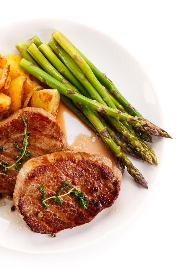 Ψημένες στη σχάρα μπριζόλες, τσιπ και σπαράγγι βόειου κρέατος στοκ εικόνα