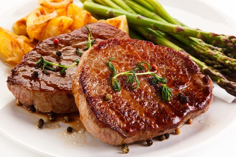 Ψημένες στη σχάρα μπριζόλες, τσιπ και σπαράγγι βόειου κρέατος στοκ εικόνες με δικαίωμα ελεύθερης χρήσης
