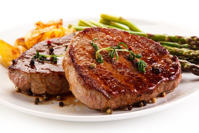 Ψημένες στη σχάρα μπριζόλες, τσιπ και σπαράγγι βόειου κρέατος στοκ φωτογραφία