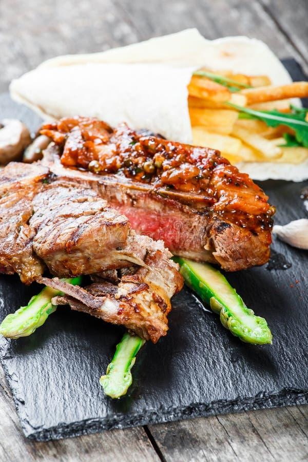 Ψημένες στη σχάρα μπριζόλες χοιρινού κρέατος με τα χορτάρια, το σπαράγγι, το σκόρδο, τα μανιτάρια και τα τηγανητά πατατών στο υπό στοκ εικόνες με δικαίωμα ελεύθερης χρήσης