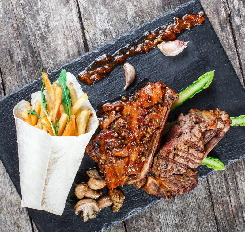 Ψημένες στη σχάρα μπριζόλες χοιρινού κρέατος με τα χορτάρια, το σπαράγγι, το σκόρδο, τα μανιτάρια και τα τηγανητά πατατών στο υπό στοκ φωτογραφία με δικαίωμα ελεύθερης χρήσης