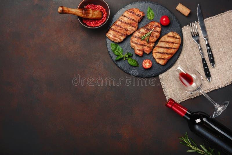 Ψημένες στη σχάρα μπριζόλες χοιρινού κρέατος στην πέτρα με το μπουκάλι του κρασιού, του γυαλιού κρασιού, του μαχαιριού και του δι στοκ εικόνες