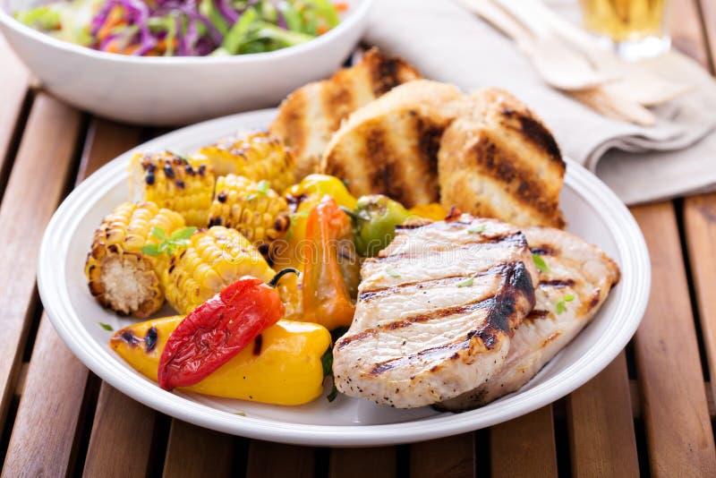 Ψημένες στη σχάρα μπριζόλες χοιρινού κρέατος με τα λαχανικά και το ψωμί στοκ εικόνες
