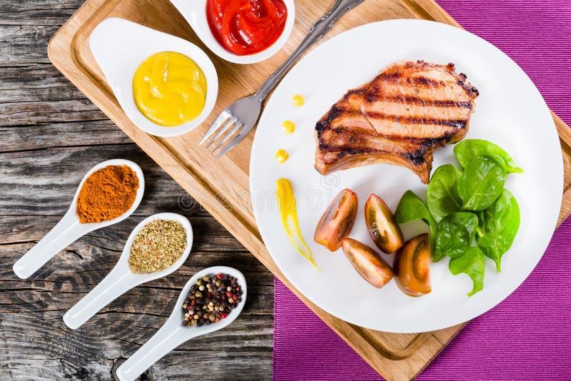 Ψημένες στη σχάρα μπριζόλες χοιρινού κρέατος στο άσπρο πιάτο, τοπ άποψη στοκ εικόνες