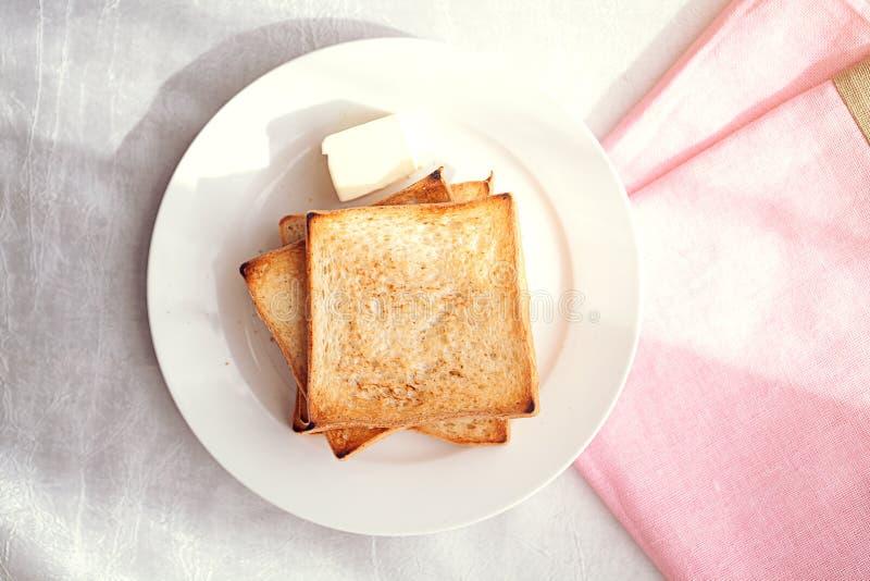 Ψημένες φέτες ψωμιού με το βουτύρου ελαφρύ κτύπημα για το πρόγευμα στοκ εικόνες