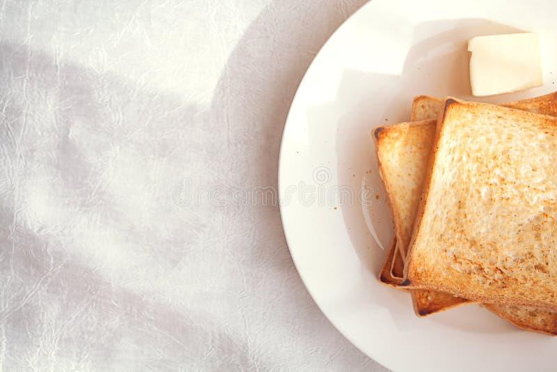 Ψημένες φέτες ψωμιού με το βουτύρου ελαφρύ κτύπημα για το πρόγευμα στοκ εικόνα