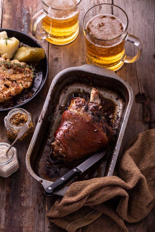Ψημένη άρθρωση χοιρινού κρέατος με την μπύρα και κουνουπίδι στο τηγάνι ψητού στοκ εικόνα με δικαίωμα ελεύθερης χρήσης