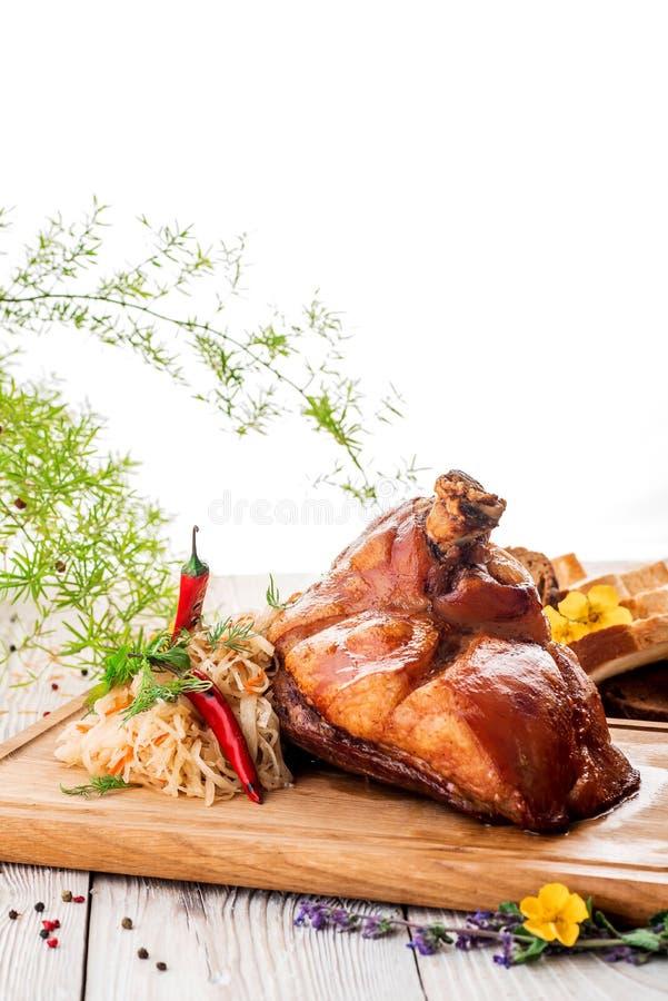 Ψημένη άρθρωση χοιρινού κρέατος με το αργό βρασμένο λάχανο και πιπέρι στον ξύλινο τέμνοντα πίνακα κλείστε επάνω απομονωμένος στοκ εικόνα