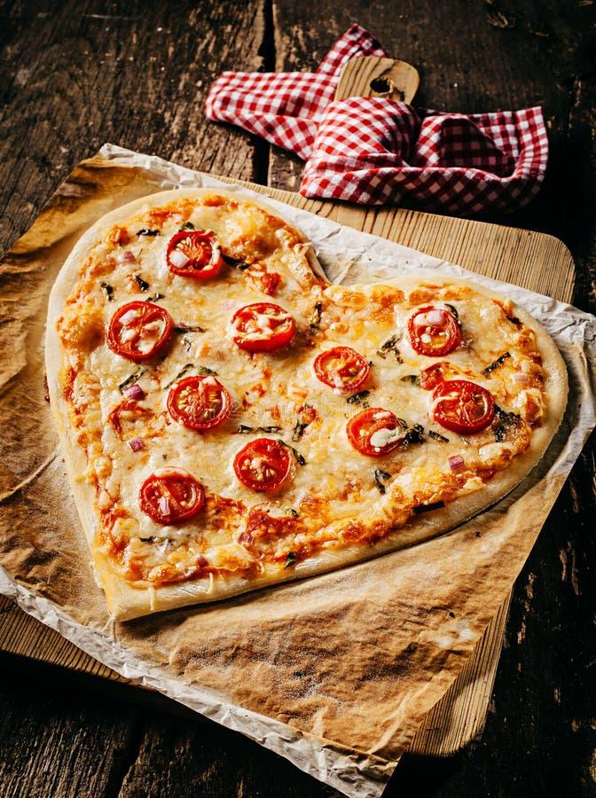 Ψημένη καρδιά-διαμορφωμένη πίτσα που ολοκληρώνεται με τις φέτες ντοματών στοκ φωτογραφία με δικαίωμα ελεύθερης χρήσης