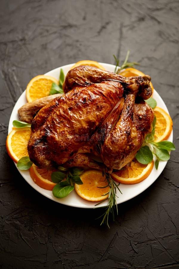 Ψημένη ολόκληρη κοτόπουλο ή Τουρκία που εξυπηρετείται στο άσπρο κεραμικό πιάτο με τα πορτοκάλια στοκ φωτογραφία