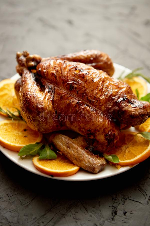 Ψημένη ολόκληρη κοτόπουλο ή Τουρκία που εξυπηρετείται στο άσπρο κεραμικό πιάτο με τα πορτοκάλια στοκ εικόνες