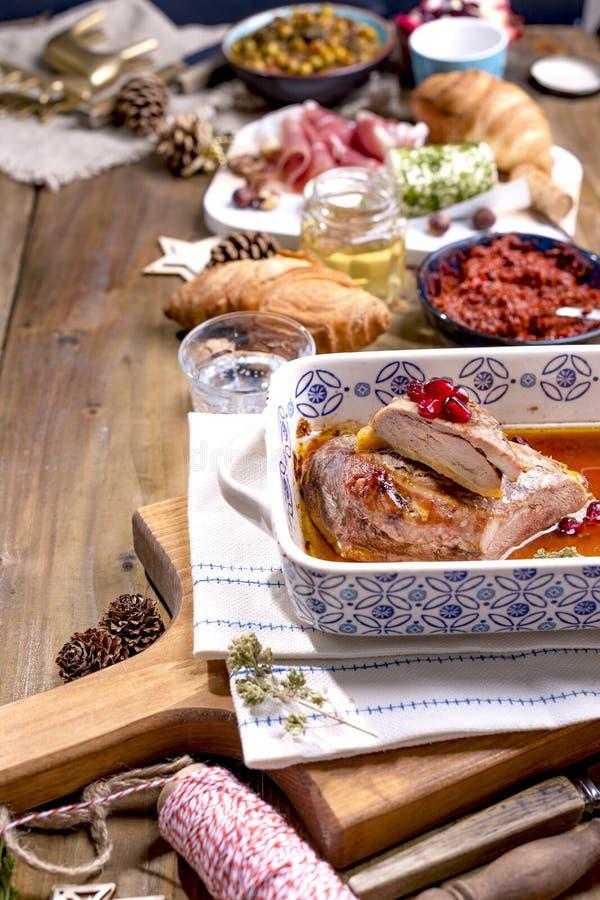 Ψημένη πάπια και διάφορα πρόχειρα φαγητά για τον πίνακα Χριστουγέννων Αγροτικός πίνακας με το ντεκόρ και διαφορετικά τρόφιμα για  στοκ φωτογραφία με δικαίωμα ελεύθερης χρήσης