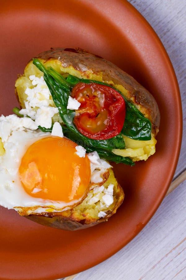 Ψημένη πατάτα με το τηγανισμένο κεράσι αυγών, φέτας, σπανακιού και ντοματών στοκ εικόνα