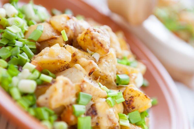 Ψημένη πατάτα με το τυρί και πράσινα σε ένα πιάτο στοκ φωτογραφία με δικαίωμα ελεύθερης χρήσης