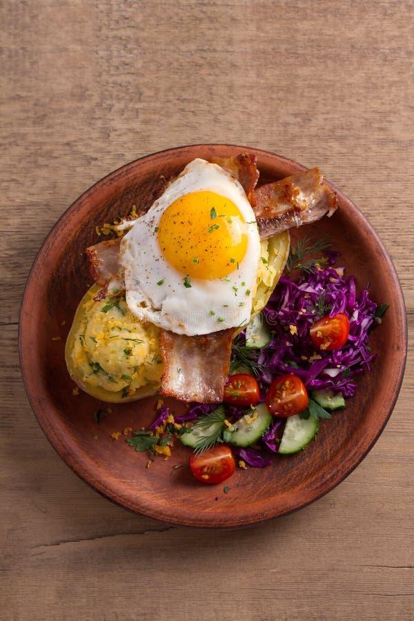 Ψημένη πατάτα στο σακάκι που φορτώνεται με το τυρί και που ολοκληρώνεται με το μπέϊκον και τηγανισμένο αυγό στο πιάτο με τα λαχαν στοκ εικόνα