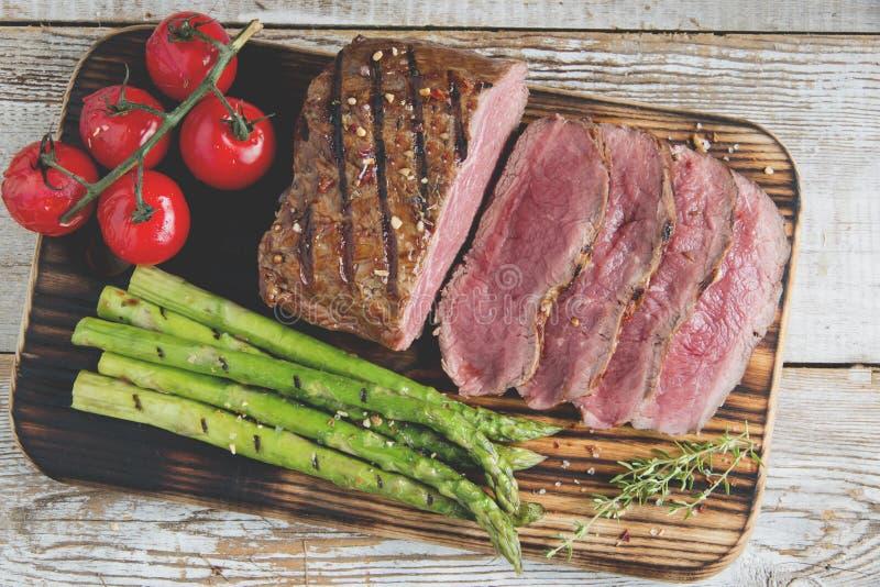 Ψημένη στη σχάρα μπριζόλα βόειου κρέατος που τεμαχίζει μέσο σπάνιο, σπαράγγι, ντομάτα στοκ φωτογραφίες με δικαίωμα ελεύθερης χρήσης