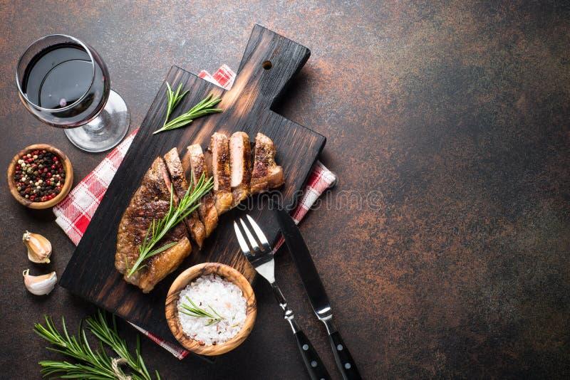 Ψημένη στη σχάρα μπριζόλα βόειου κρέατος striploin με το γυαλί κόκκινου κρασιού στοκ εικόνες