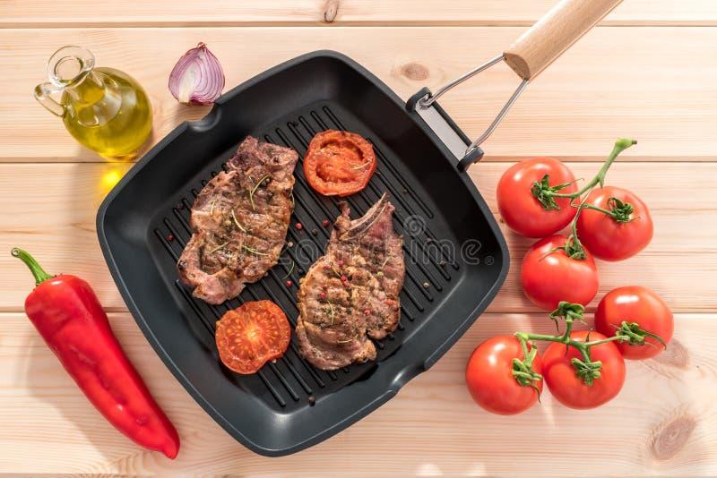 Ψημένη στη σχάρα μπριζόλα στο τηγάνι σχαρών με τις ντομάτες στοκ εικόνες