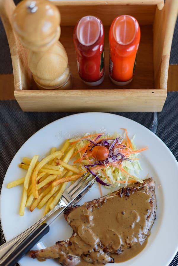 Ψημένη στη σχάρα μπριζόλα χοιρινού κρέατος με τη μαύρη σάλτσα, τα λαχανικά και τις τηγανιτές πατάτες πιπεριών στοκ εικόνα