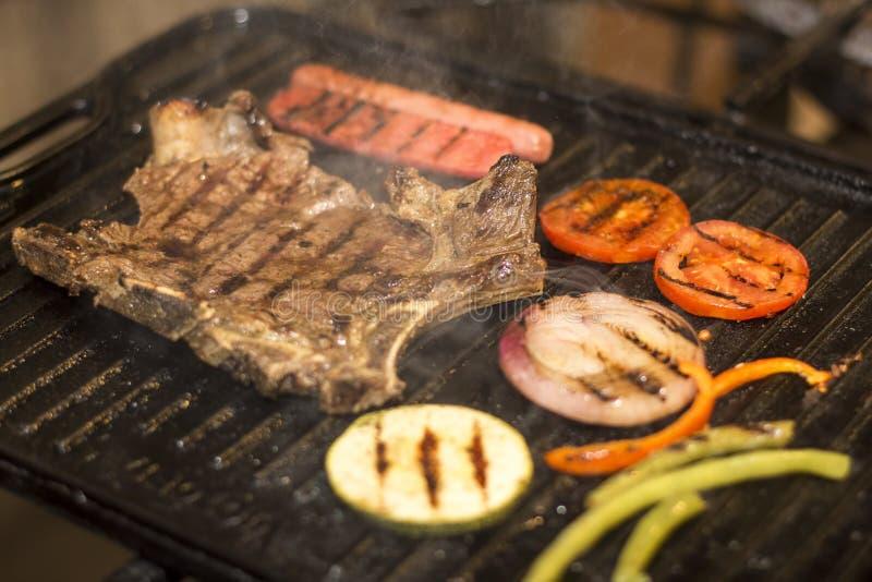 Ψημένη στη σχάρα μπριζόλα βόειου κρέατος με το λουκάνικο, μικτά ψημένα λαχανικά στοκ εικόνα με δικαίωμα ελεύθερης χρήσης