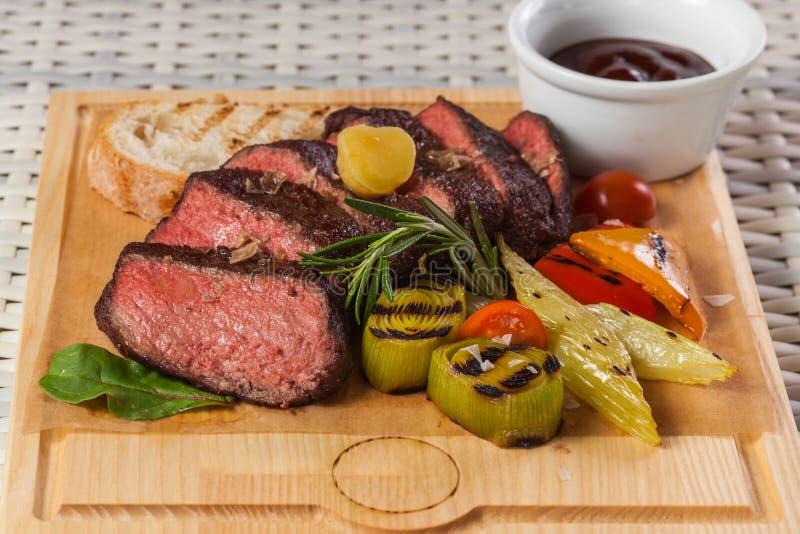 Ψημένη στη σχάρα μπριζόλα βόειου κρέατος στον ξύλινο πίνακα στοκ φωτογραφίες με δικαίωμα ελεύθερης χρήσης