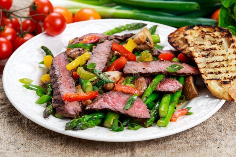 Ψημένη στη σχάρα μπριζόλα με τα ανακατώνω-τηγανισμένα λαχανικά στο πιάτο στοκ εικόνες