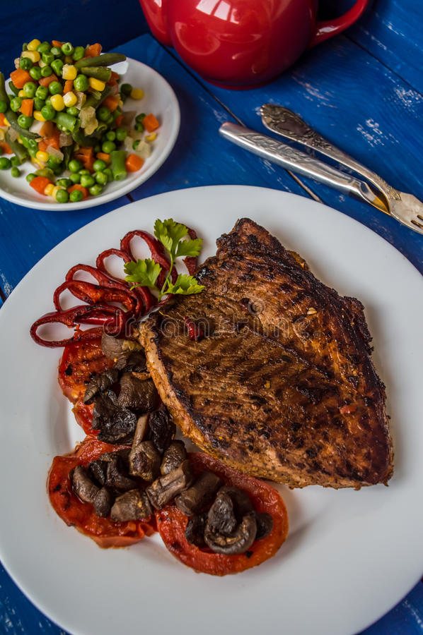 Ψημένη στη σχάρα μπριζόλα με τα μανιτάρια, τις ντομάτες και τα πιπέρια σε ένα άσπρο πιάτο Ξύλινο μπλε υπόβαθρο Τοπ όψη στοκ φωτογραφίες
