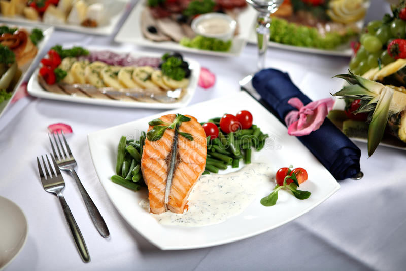 Ψημένη στη σχάρα μπριζόλα σολομών με τα πράσινα φασόλια, στο διακοσμημένο να δειπνήσει πίνακα στοκ εικόνα