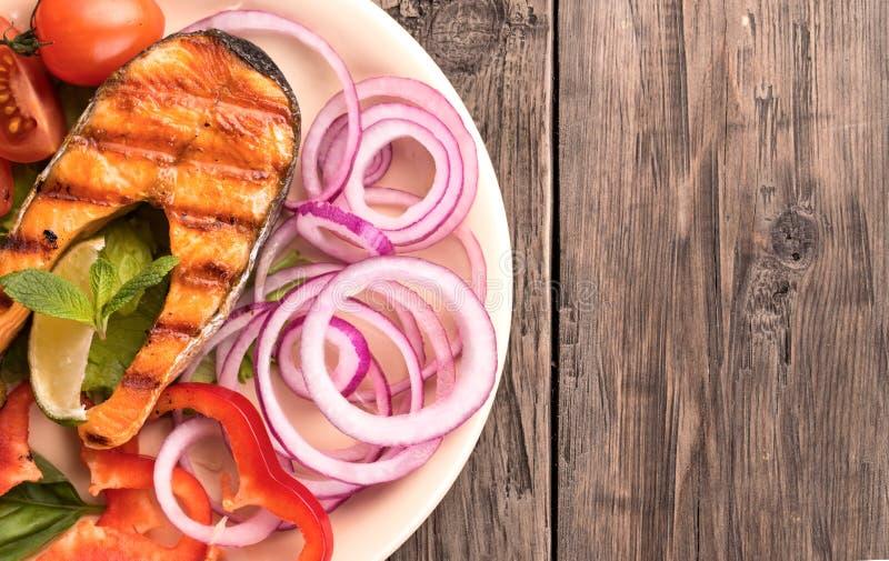 Ψημένη στη σχάρα μπριζόλα σολομών με το τεμαχισμένο κρεμμύδι και ντομάτες στο αριστερό στοκ εικόνα